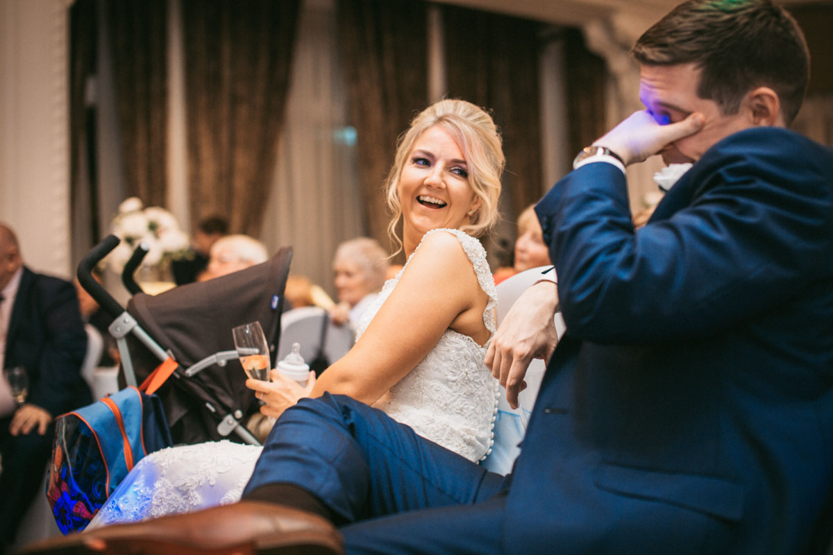 bride laughing at groom during best mans speech