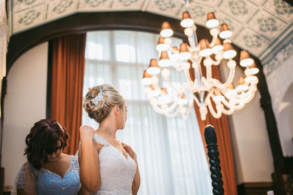 bridesmaid doing up brides dress