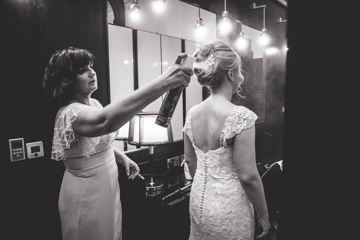 bridesmaid spraying hairspray on the brides hair