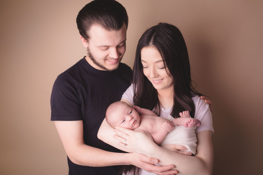 Proud new parents hold their newborn baby at liverpool newborn photography studio