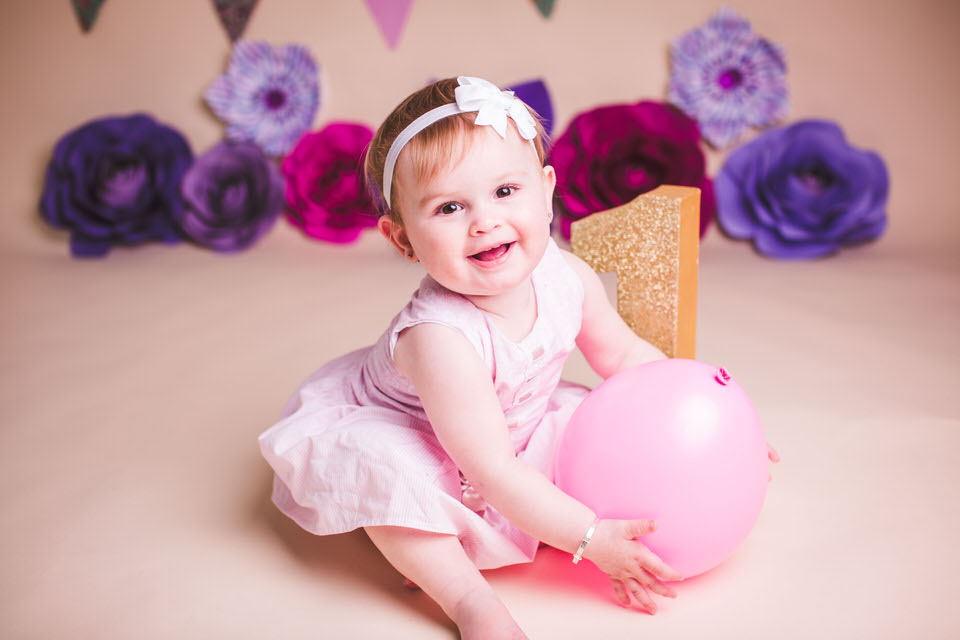 Baby girl smiling during her portrait session at liverpool studio cake smash
