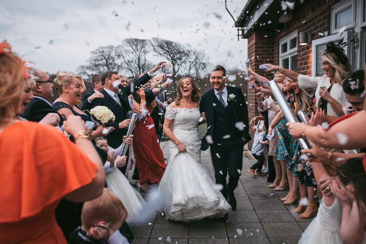 guests throw confetti at the couple on their wedding day at formby hall by liverpool wedding photographer