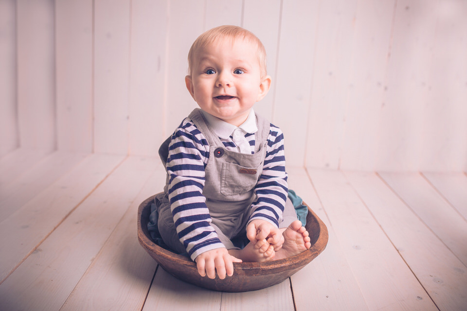 six month old sitting up in wooden bowl photo shoot in liverpool seaforth studio with family photographer