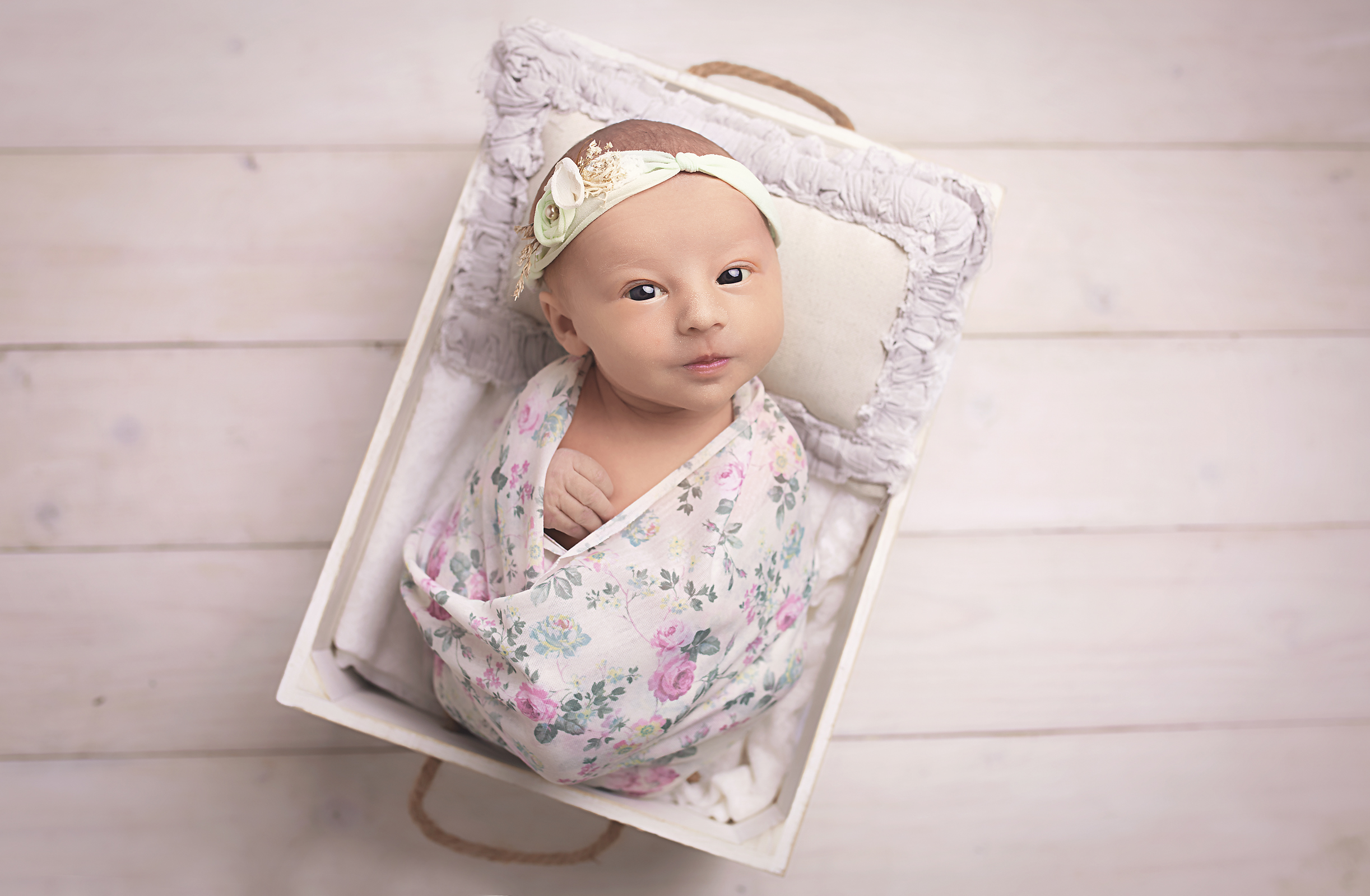 newborn baby girl in flowery wrap in a cute little box taken in liverpool photography studio