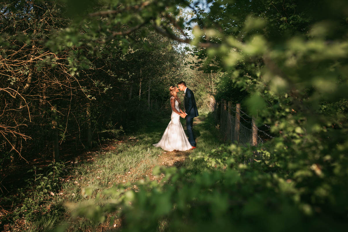 bride and groom kiss in a grassy path way at owen house wedding barn