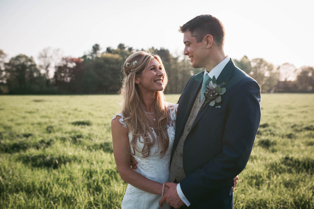 bride and groom smile at each other in a field at owen house wedding barn