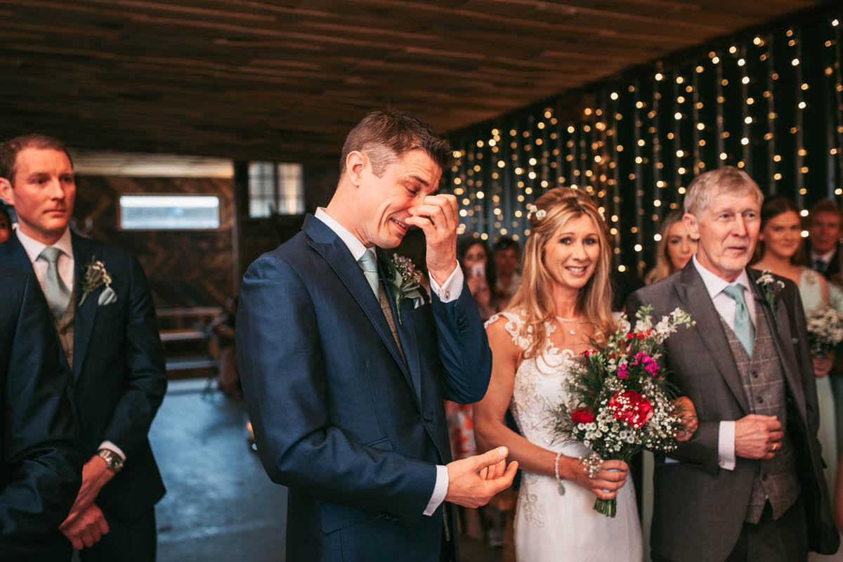 groom gets emotional as bride walks down the aisle at owen house wedding barn