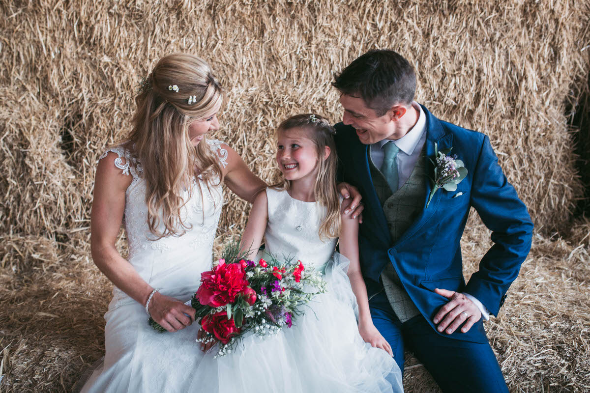 bride and groom with their daughter on the hay bales at owen house wedding barn