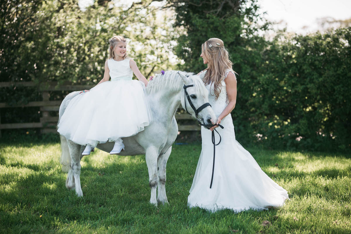 bride and her daughter with their white pony at owen house wedding barn