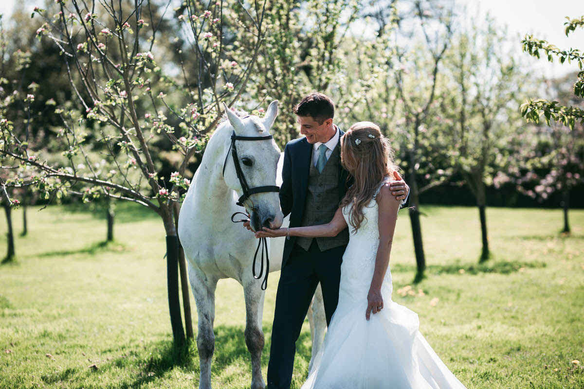 bride and groom with horse at owen house wedding barn taken by liverpool photographer