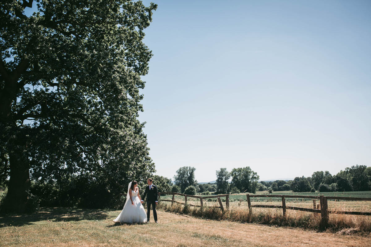 bride and groom take a stroll at willington hall in the beautiful grounds in cheshire in the lovely sunshine