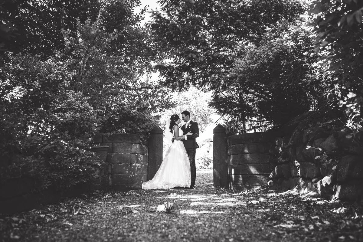 couple photos taken at willington hall in cheshire black and white photo of bride and groom in a gate way