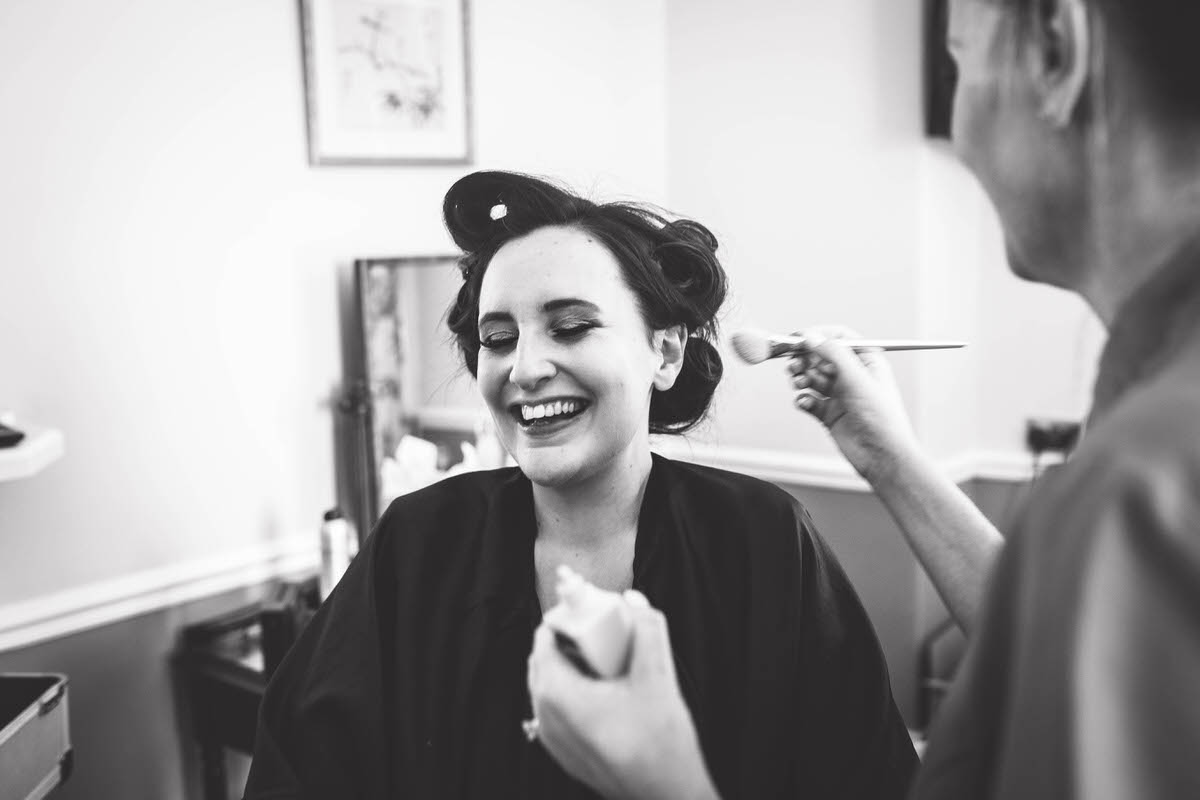 bride laughing whilst getting her make up done at willington hall cheshire phtoography