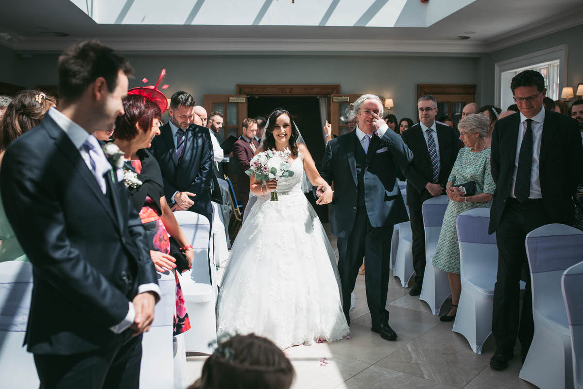 Bride walking down the aisle at willington hall in cheshire looking really happy while her dad wipes a tear from his eye