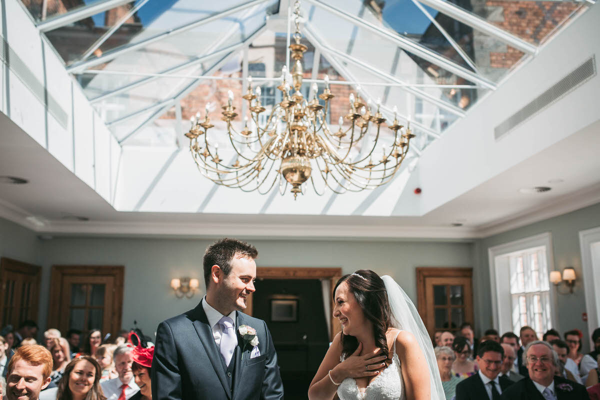 bride and groom during their wedding ceremony at willington hall in cheshire in the orengery