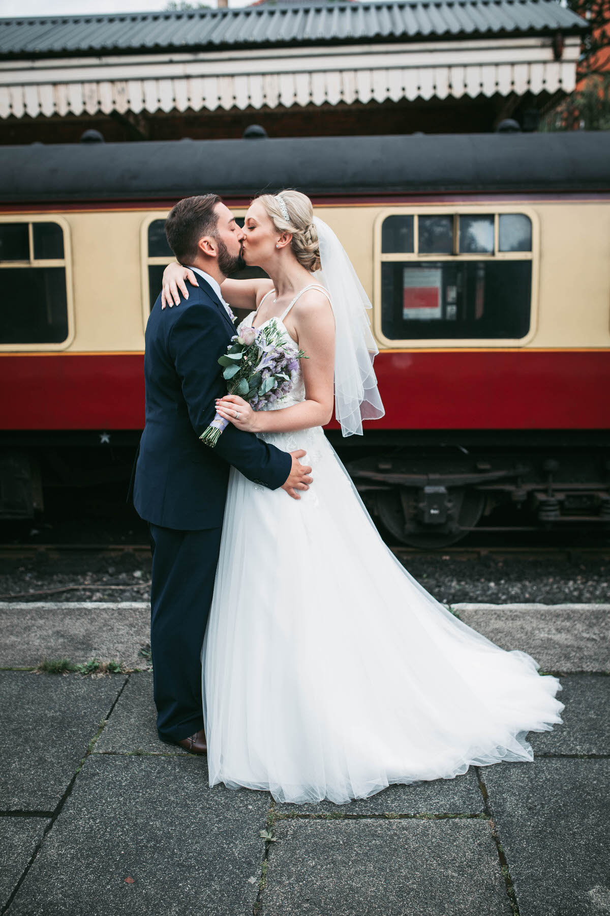 kisses in front of a train at llangollen railway station