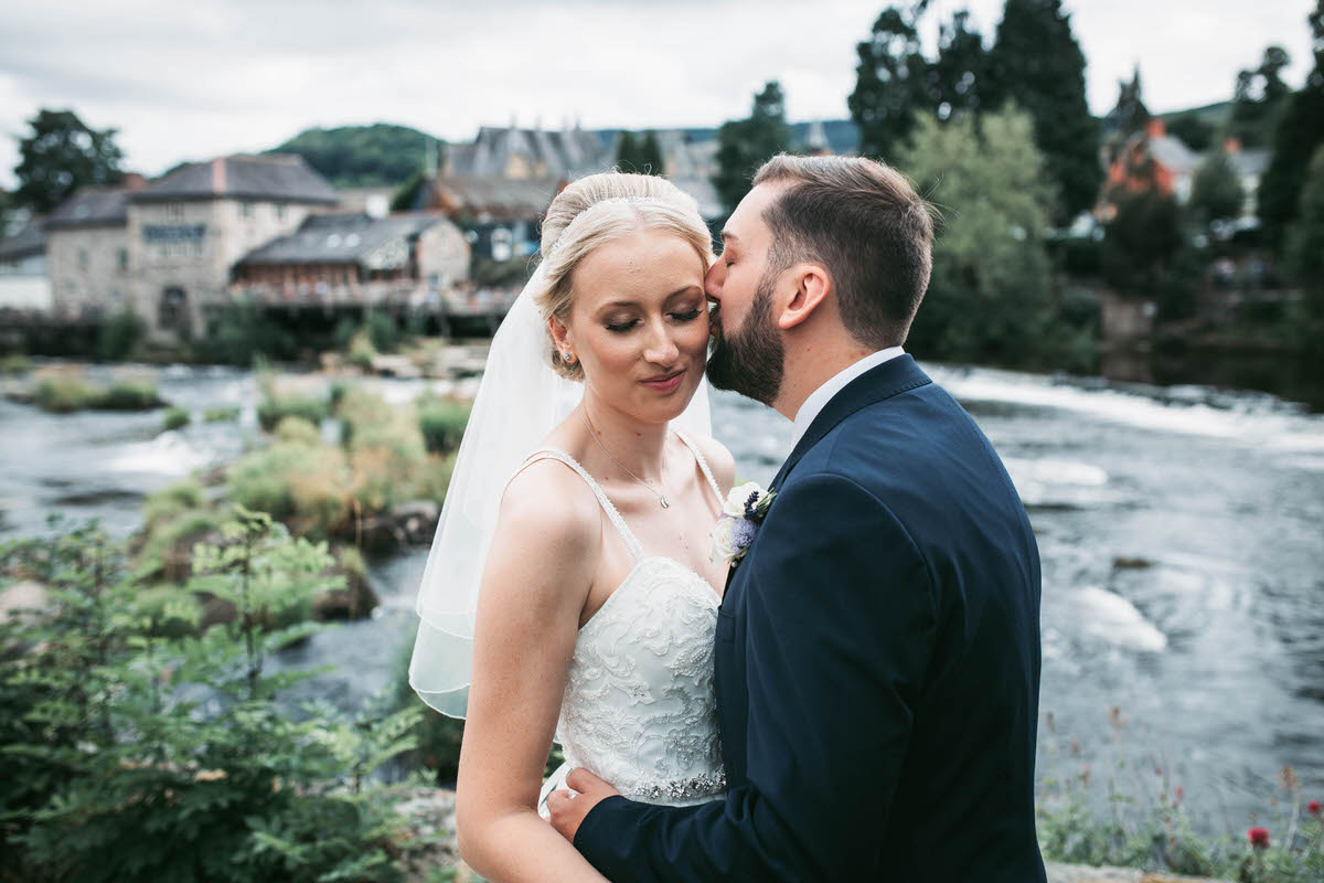 groom kisses his bride in front of the river dee at llangollen railway station