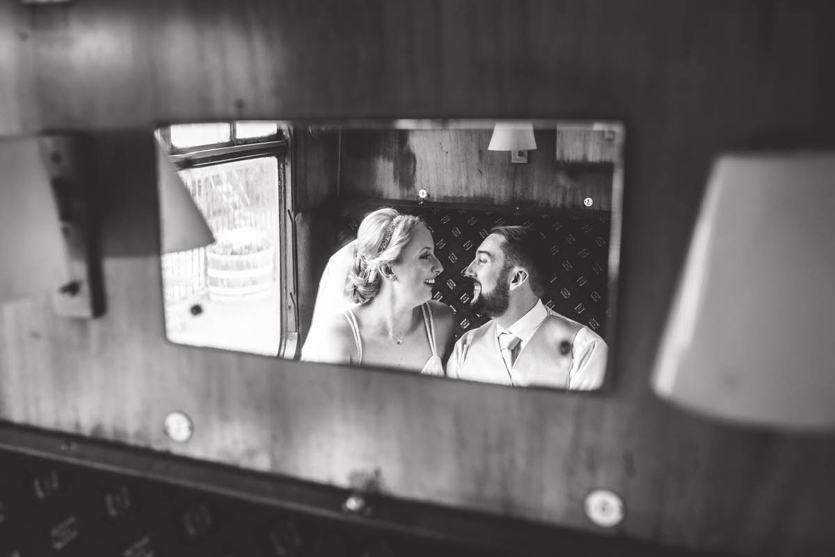 on a carriage on a train at llangollen railway station photo of bride and groom in the reflection of a mirror in black and white