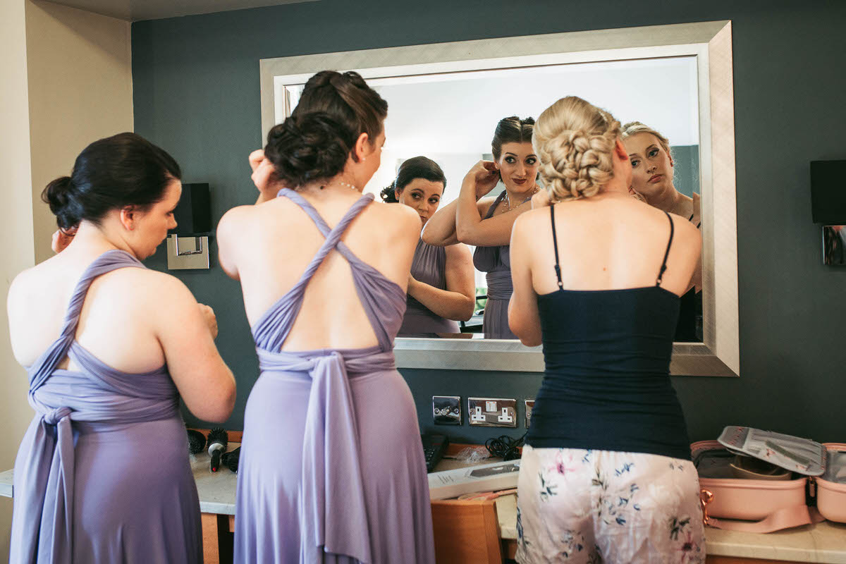 bride and her bridesmaids looking in the mirror geetting ready for the wedding at the wild pheasant hotel llangollen