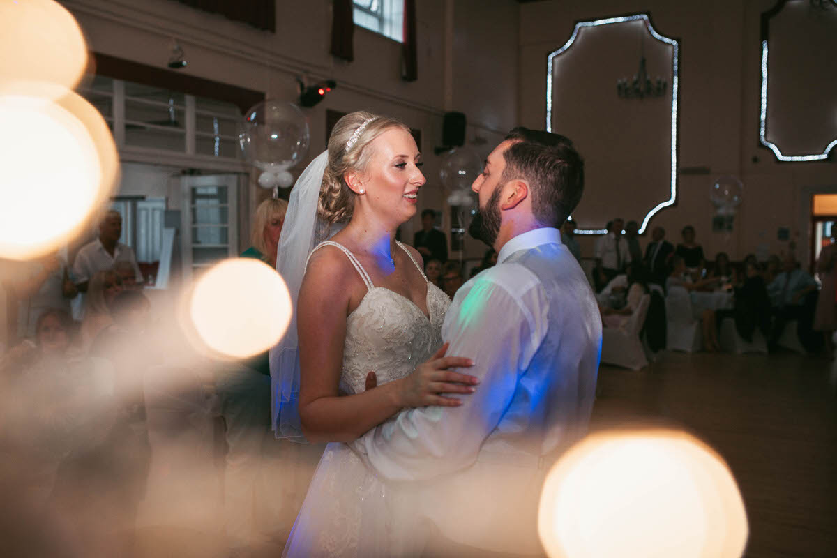 the couple have their first dance together with fairy light effects in corner of frame