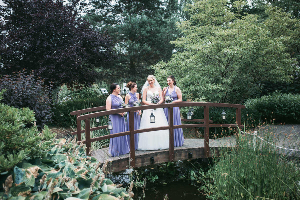 bride and bridesmaids laughing on a bride over a pond at wild pheasant hotel llangollen