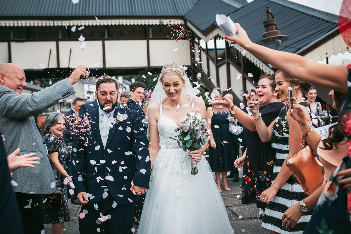 bride and groom rung through the confetti thrown by guests on the platform at llangollen railway station