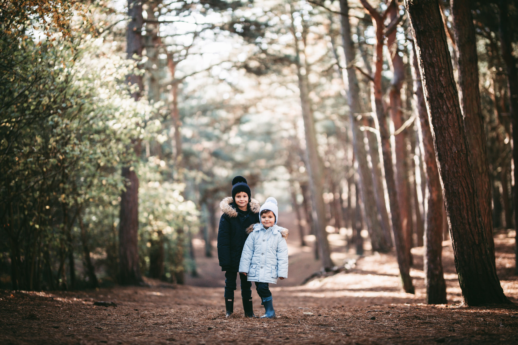two brothers standing in the tall trees at formby woods for a photo in liverpool